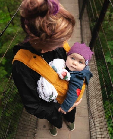 woman carrying baby on bridge